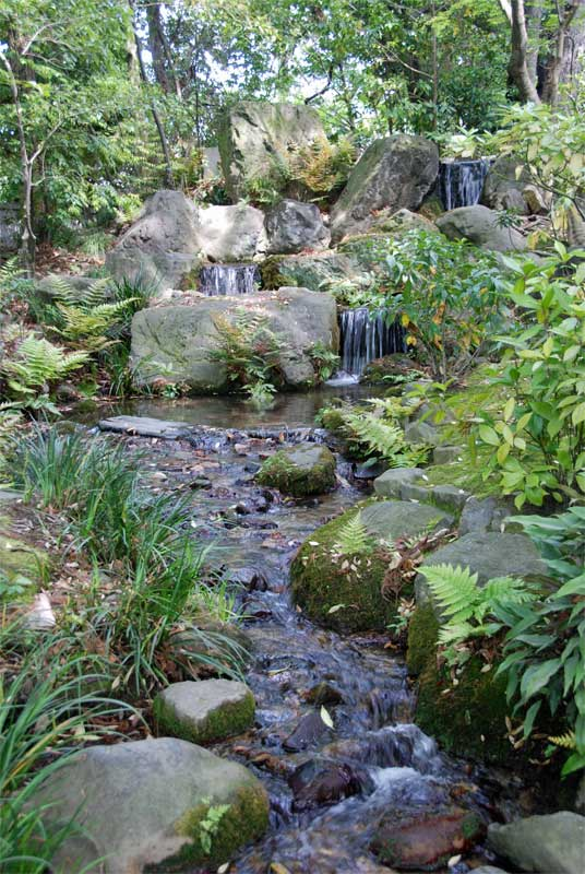 A three tiered waterfall and a stream in the garden of for Tiered pond waterfall